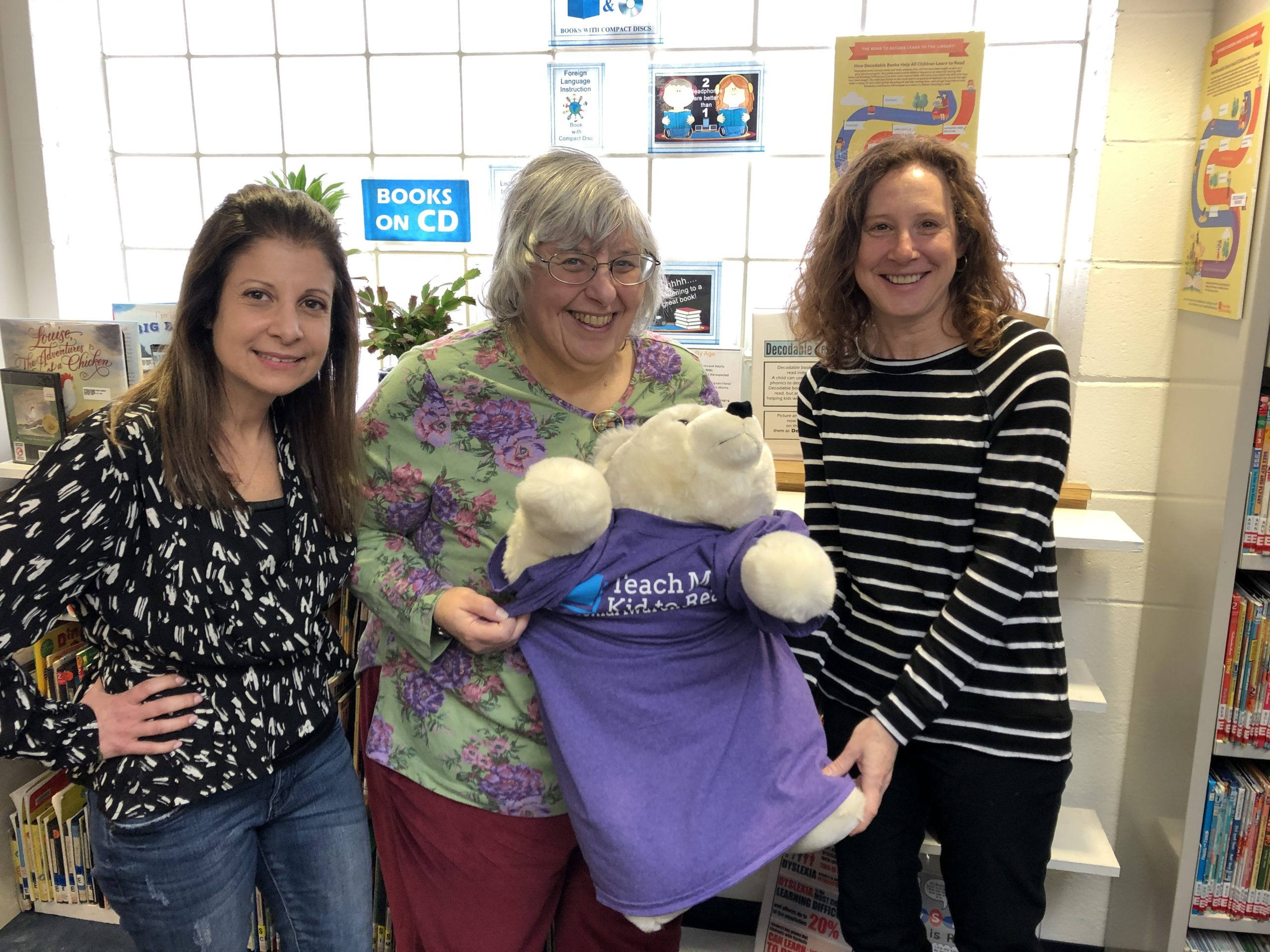 Teach My Kid to Read members and librarian Faye Lieberman, holding a stuffed bear